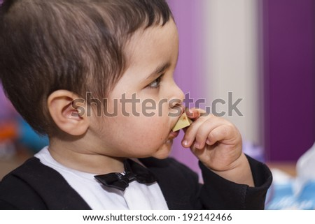 Adorable happy baby eating chocolate, wearing suit and bow tie