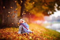 adorable happy baby girl catching the fallen leaves, playing in the autumn park