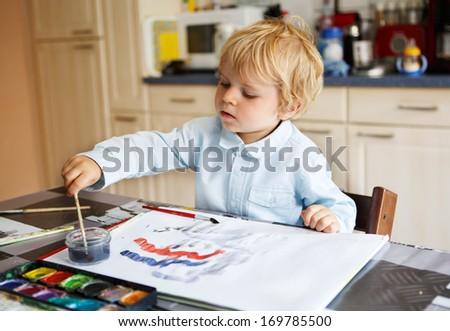 Adorable happy boy of two years drawing with paints