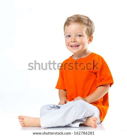 Adorable happy boy sitting on the floor in studio. Isolated of white background.