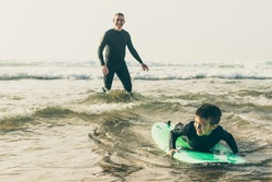 Adorable happy boy swimming on board. Happy father helping little son in wetsuit lying and swimming on surfboard on waves. Surfing concept