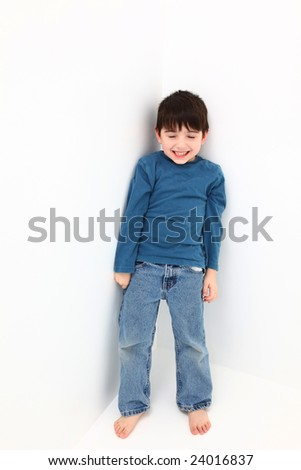 Adorable happy five year old boy standing in a white corner.