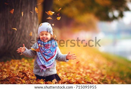 adorable happy girl playing with fallen leaves in autumn park #715095955