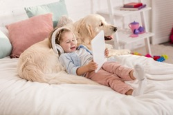 adorable happy kid listening music with tablet and leaning on golden retriever dog on bed in children room