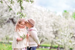 Adorable happy kids outdoors on spring day in beautiful blooming garden, little boy kissing a girl