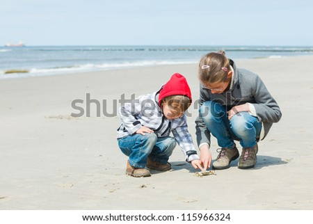 Adorable happy kids plaing with crab on the beach on spring day