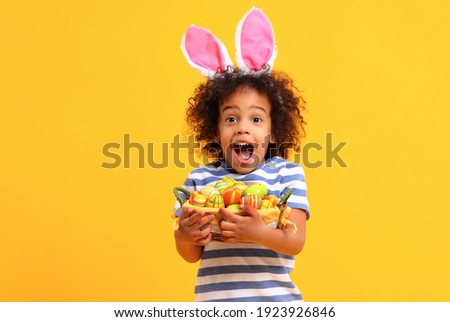 Adorable happy little African American boy with curly hair and bunny ears on head screaming with astonishment  while holding Easter basket while standing against yellow background  Photo stock ©