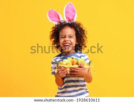 Adorable happy little African American boy with curly hair in striped t shirt  and bunny ears on head laughing while holding Easter basket Foto stock ©
