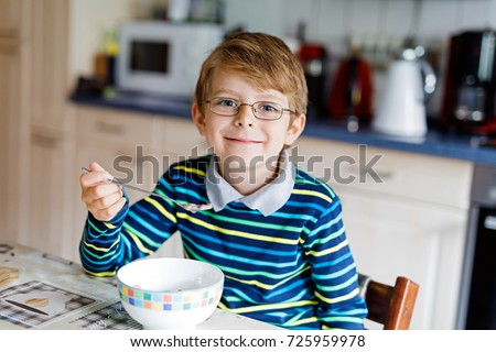 Adorable Happy little blond kid boy with glasses eating homemade cereals for breakfast or lunch. Healthy eating for children. At nursery, at school canteen or at home. #725959978