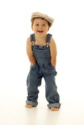 Adorable happy little boy in overalls