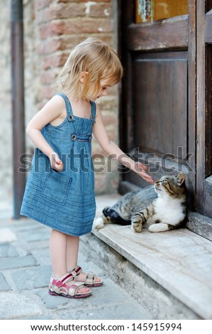 Adorable happy little girl and a cat outdoors