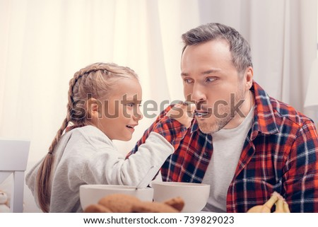 adorable happy little girl feeding father at morning - Shutterstock ID 739829023