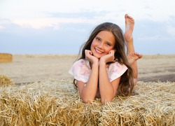 Adorable happy smiling ittle girl child lying on a hay rolls in a wheat field at sunset