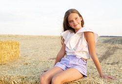 Adorable happy smiling ittle girl child sitting on a hay rolls in a wheat field at sunset