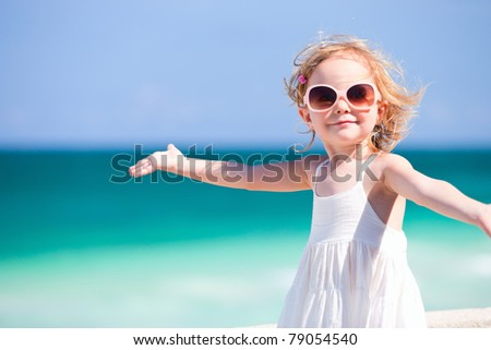 Adorable happy smiling little girl on beach vacation