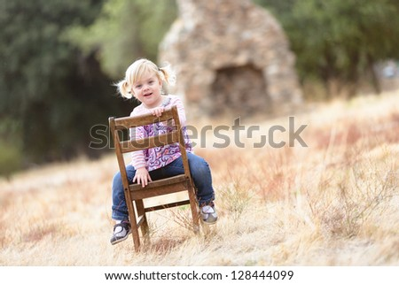 adorable happy toddler sitting in a field