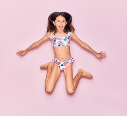 Adorable hispanic child girl on vacation wearing bikini surprised with open mouth. Jumping over isolated pink background