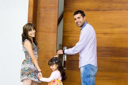 Adorable hispanic family of three posing for camera outside front entrance door while entering house.