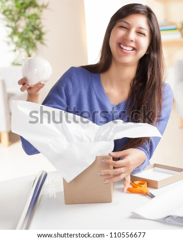 Adorable Hispanic woman wrapping gift with silver wrapping paper and brown box  in living room at table wearing blue shirt.