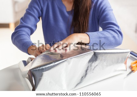 Adorable Hispanic woman wrapping gift with silver wrapping paper in living room at table wearing blue shirt.