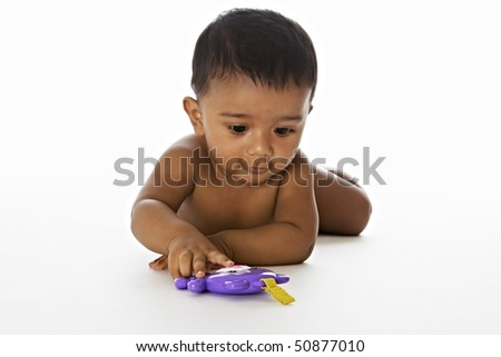 Adorable Indian baby lying on floor and playing with a toy, isolated on white background.