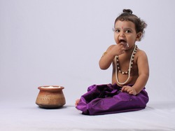Adorable Indian kid dressed up as little krishna  Shrikrishna or kanha kanhaiya on fancy dress Gokulashtami festival. eating curd butter