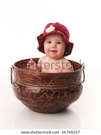 Adorable infant wearing a crochet hat and sitting in a metal planter, isolated on white.