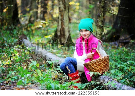 Adorable kid girl in pink vest, white sweater, green hat and boots with basket picking mushrooms in autumn forest at sunny day