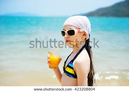 Adorable kid girl in swimsuit  drinking juice on the beach - Shutterstock ID 423208804