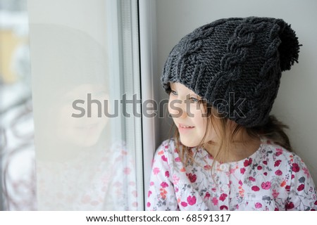 Adorable kid girl with big eyes in dark grey knit hat near the window