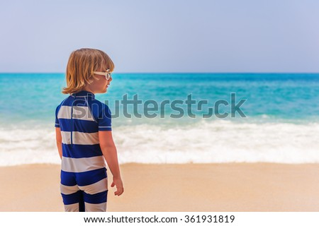 Adorable kid having fun on summer vacation, playing by the sea, back view,  image taken in Tropea, Calabria, Italy #361931819