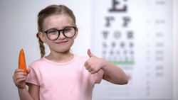 Adorable kid in glasses showing thumbs up to carrot, beta-carotene for eyes