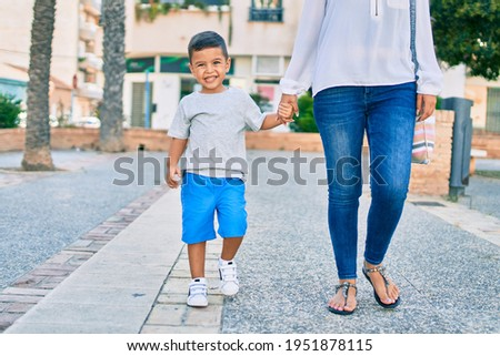 Adorable latin mother and son walking at the city.