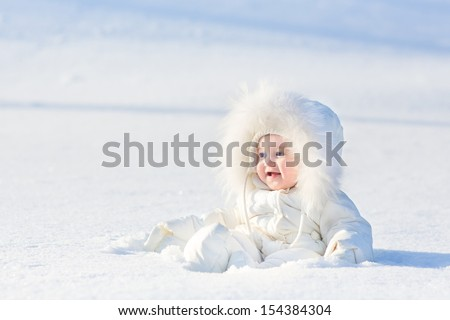 Adorable laughing baby girl in a warm white snow suit playing in snow on a very sunny and clear winter day in a park