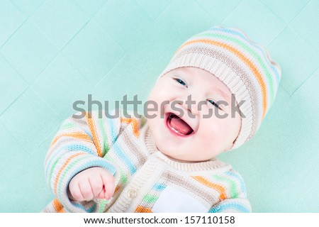 Adorable laughing baby wearing a warm knitted jacket and hat relaxing on a green blanket