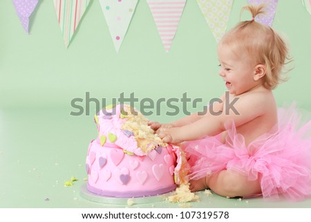 Adorable laughing blond haired baby girl with pony tail in pink tutu touching vanilla sponge cake with pink and purple fondant heart icing while sitting on green background with flag bunting behind