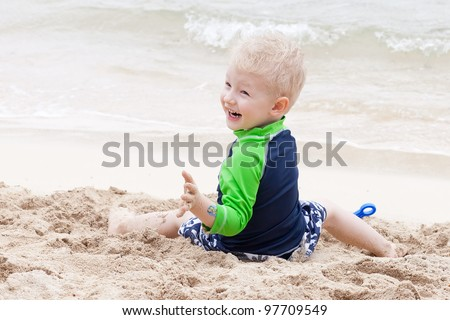 adorable laughing toddler at the tropical beach - stock photo