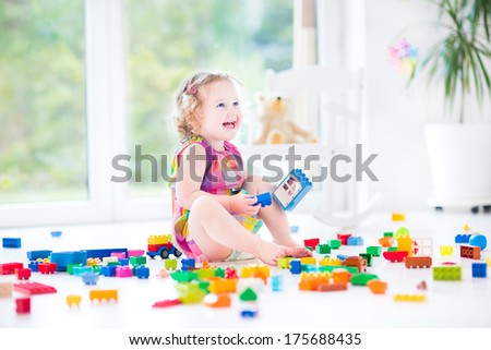 Adorable laughing toddler girl playing with colorful blocks sitting on a floor in a sunny bedroom with a big window