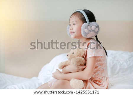 Adorable little Asian child girl wearing winter earmuffs and hugging teddy bear while sitting on the bed at home. #1425551171