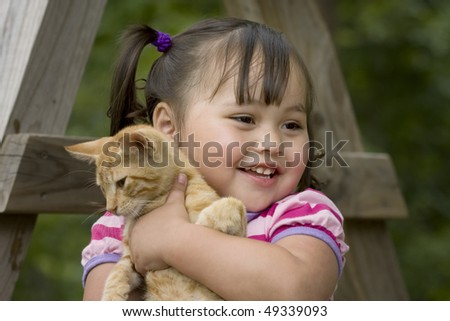 Adorable little asian girl giving her orange kitten a hug