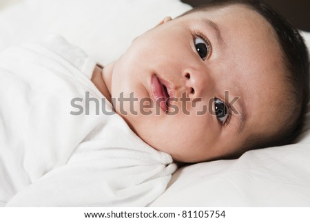 Adorable little baby girl after waking up in the bed. little baby thinking about something, wearing white shirt and laying in the bed with white bed sheet.