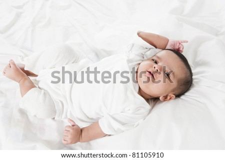 Adorable little baby girl laying in the bed after waking up. Portrait of a smiling new born baby girl