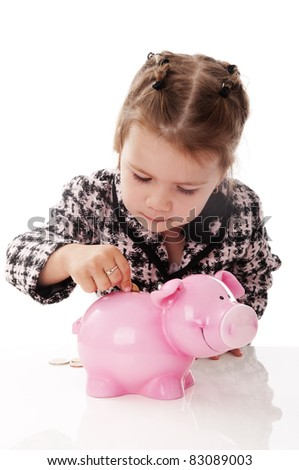 Adorable little baby girl playing with money pig