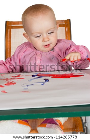 Adorable little baby girl sitting at a table finger painting with her fingers daubed with red pigment which she is happily painting onto a sheet of paper