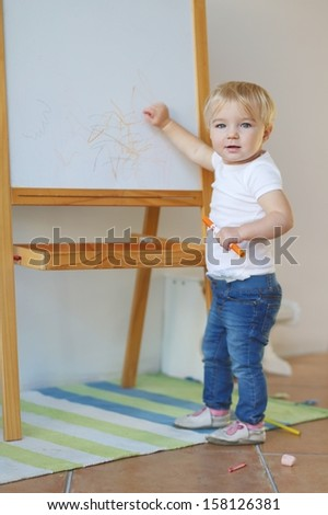 Adorable little blond baby girl draws with colorful orange crayon on a white board