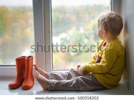 Adorable little blond kid boy sitting on the windowsill with rain shoes and looking on autumn raindrops, indoors. A child looks out the window. Vintage color.  orange rubber boots standing near window