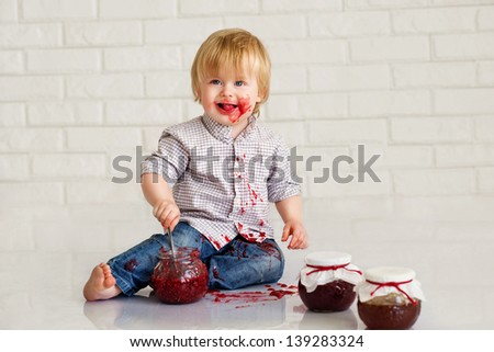 Adorable little boy got messy eating strawberry jam from glass jars