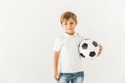 adorable little boy holding soccer ball and smiling at camera isolated on white