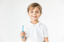 adorable little boy holding toothbrush and smiling at camera isolated on white