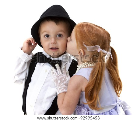 Adorable little boy holds on to his hat as a pretty little girl kisses his cheek